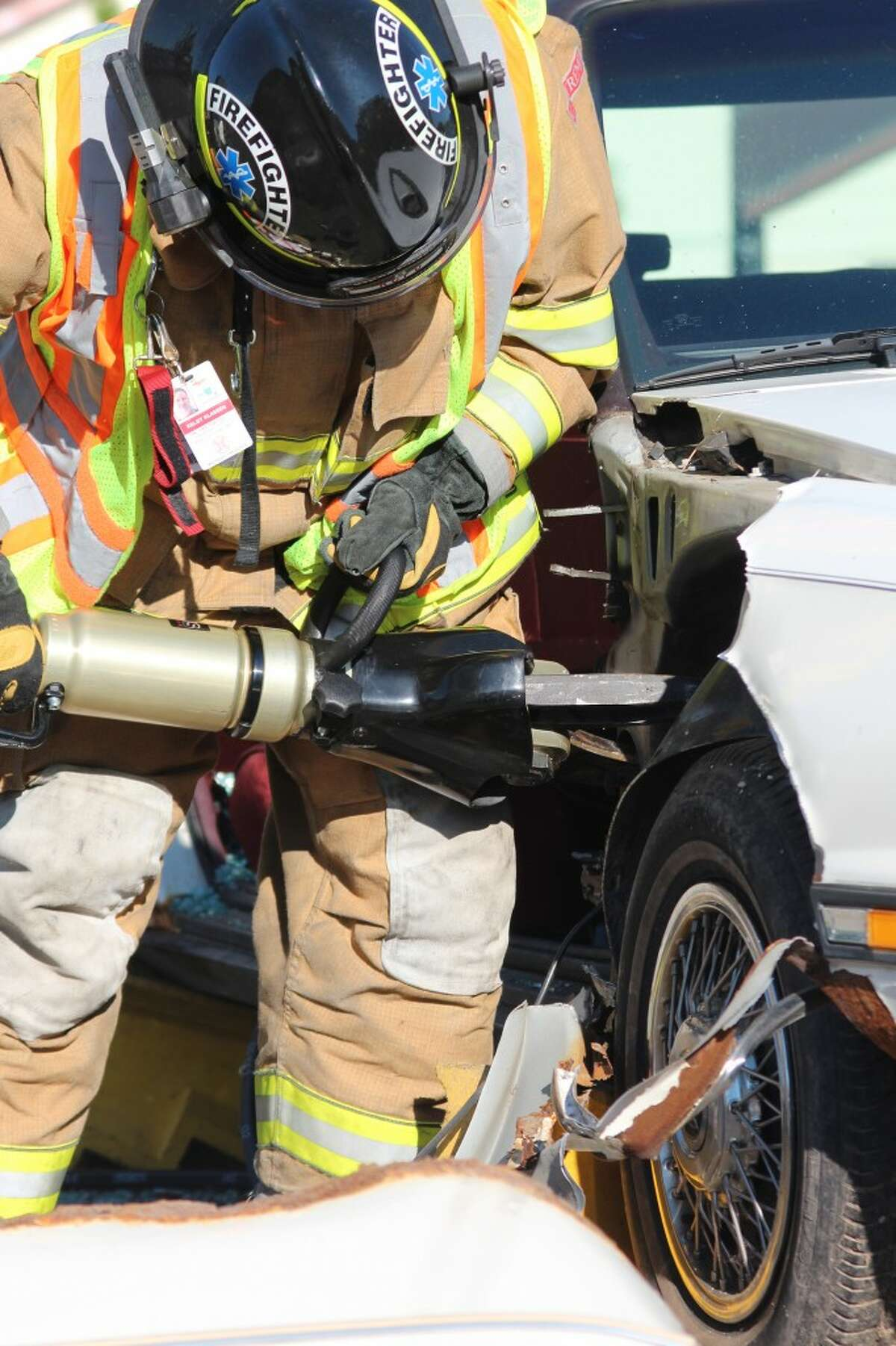 CLEAN CUT: Firefighters from the Reed City Fire Department uses a new hydraulic rescue tool to cut through a donated demo car during a practice exercise Tuesday. The new tools were purchased with a $16,000 AAA grant. (Herald Review photo/Sarah Neubecker)