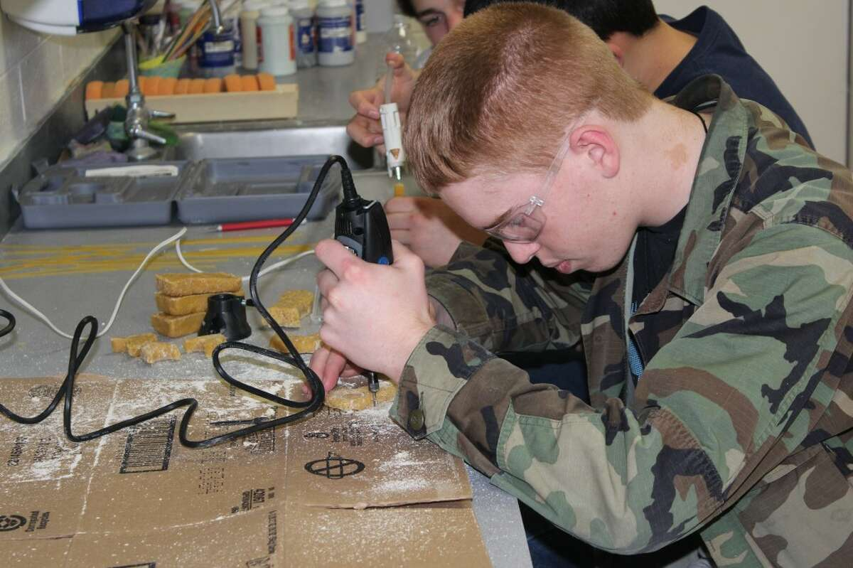 Chester Essner uses a drill to carve a hole in the noodle and glue mixture for Evart High School's Falkirk Bridge replica. Essner and his team will compete this weekend at Ferris State University's 14th Annual Spaghetti Bridge Competition. (Pioneer photo/ Lauren Gentile)