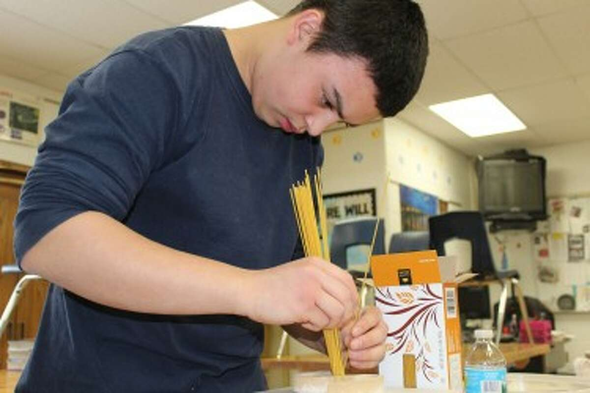 """MORE THAN NOODLES: Paul Gaffney plans to use spaghetti noodles and hot glue to create a rod to hold together part of the Falkirk Wheel bridge replica. Gaffney is a member of the """"Pasta PACCK"""" from Evart High School competing in Ferris State University's 14th Annual Spaghetti Bridge Competition this weekend. (Pioneer photos/Lauren Gentile)"""