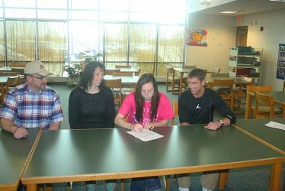 SIGNING ON: Attending the signing ceremonies for Erica Buchner last week at Pine River were, at left, her parents, David and Serena Crawford, and at right, Ty McGregor, coach at Kirtland Community College. (Herald Review/John Raffel)