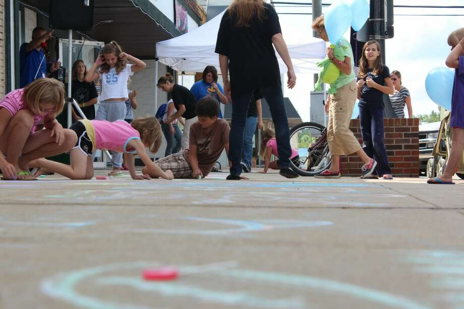 CHALK FESTIVAL: More than 100 children and adults chalked downtown Evart for the Evart Chalk Festival Tuesday morning. The festival was sponsored by the Evart Downtown Development Authority and Movies N' More. (Herald Review photo/Sarah Neubecker)