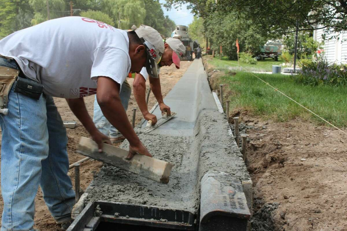 NEW CURBS: Workers install curbs on Church Avenue on Aug. 15 after completing underground water/sewer line upgrades. The road is scheduled to be paved before school starts Sept. 1. (Herald Review photos/Sarah Neubecker)
