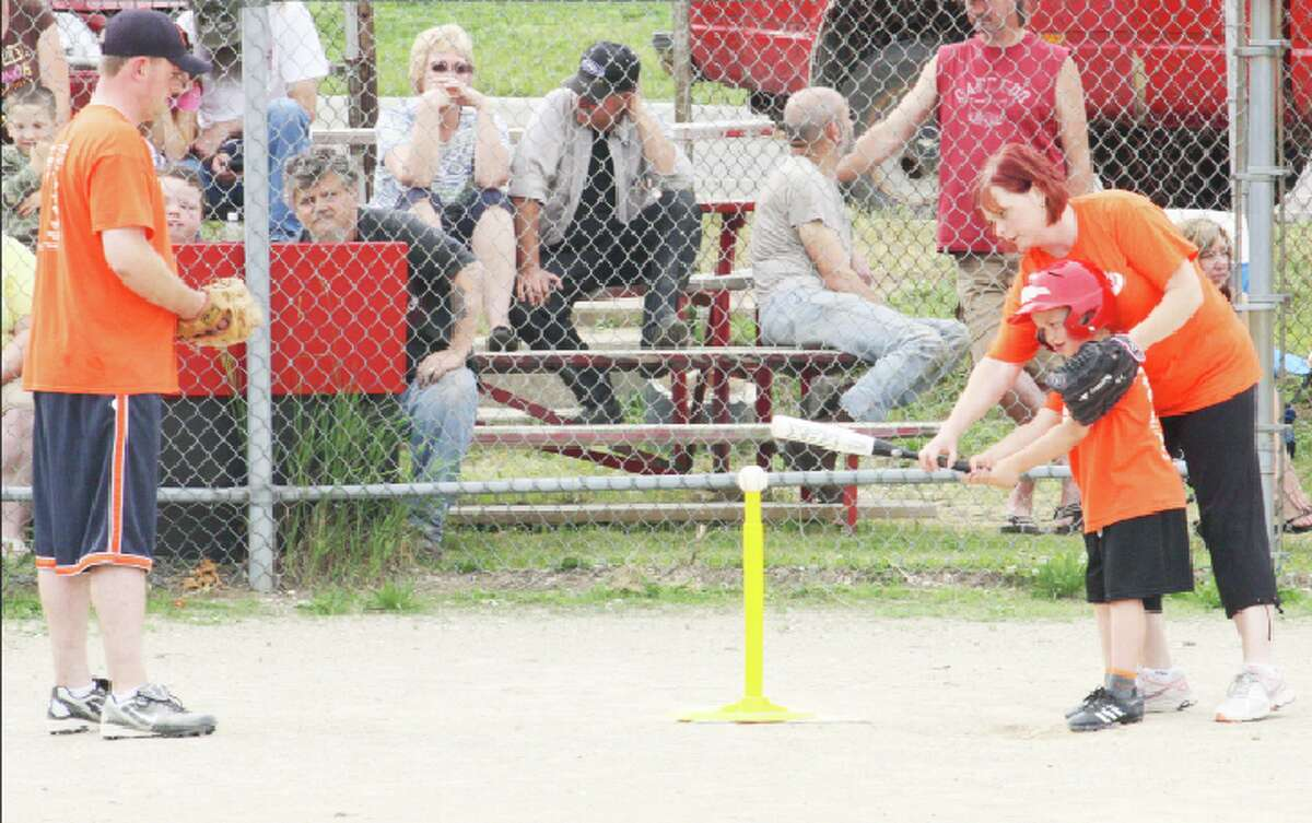 LIttle LEague: (ABOVE) David Dozier, left, watches as a T-Baller works on his swing last week during Reed City Little League action. (Herald Review/John Raffel)