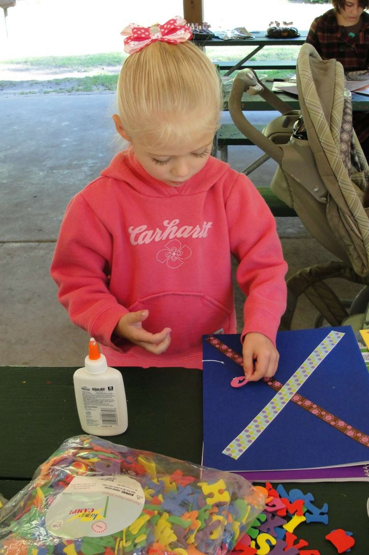 PERSONAL TOUCH: Caelyn, age 4, using foam letters to personalize her folder. (Herald Review photos/Shannon Hartley)