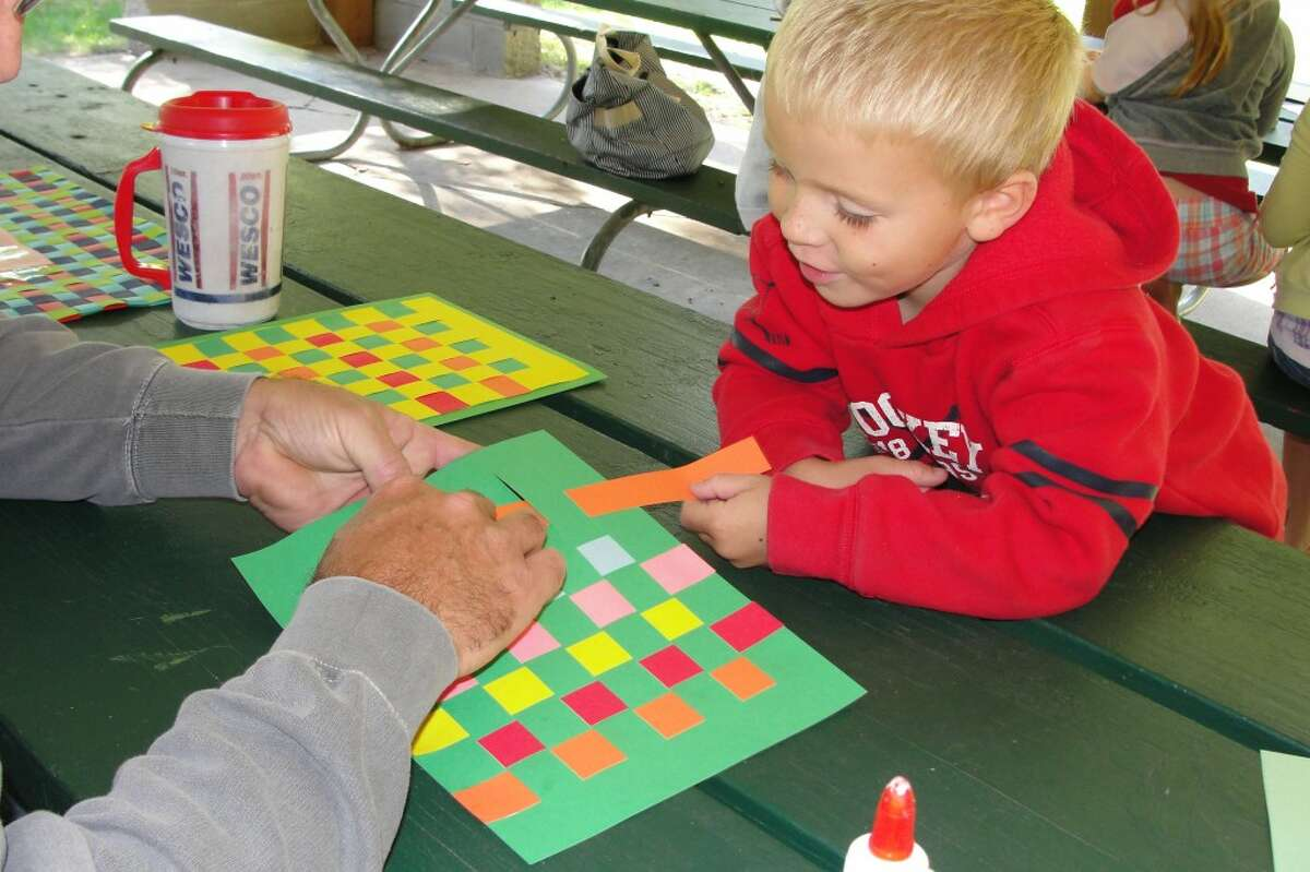 WEAVING: Nicolas, 4, creates a weaving project at the last Art in the Park in Reed City Saturday