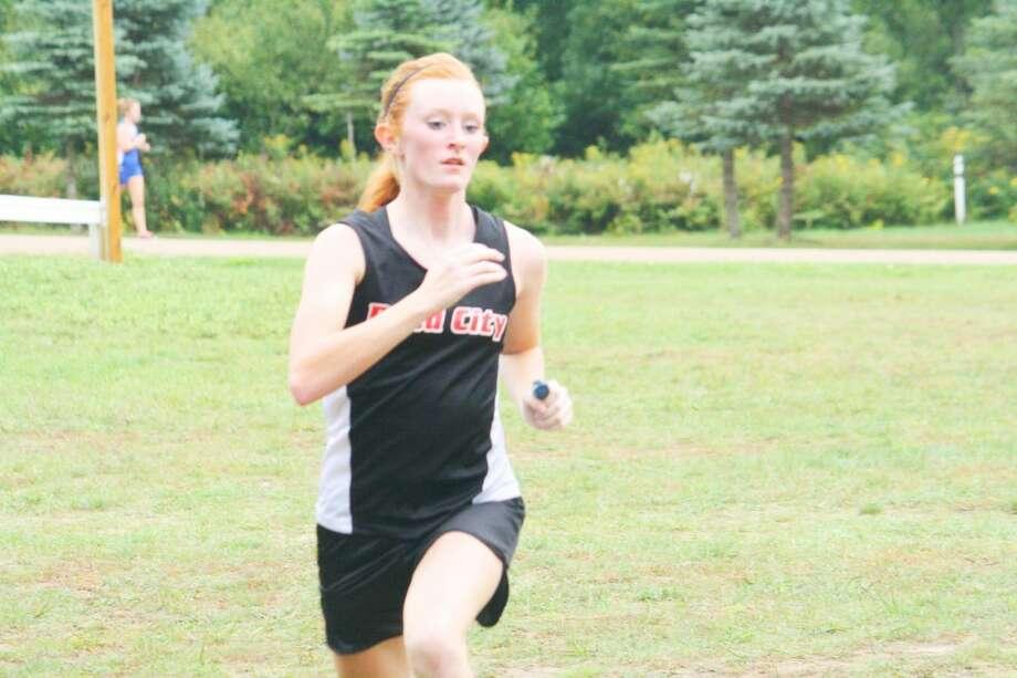 Lindsey Greer of Reed City crosses the finish line last Friday against Evart. (Herald Review photo/John Raffel)