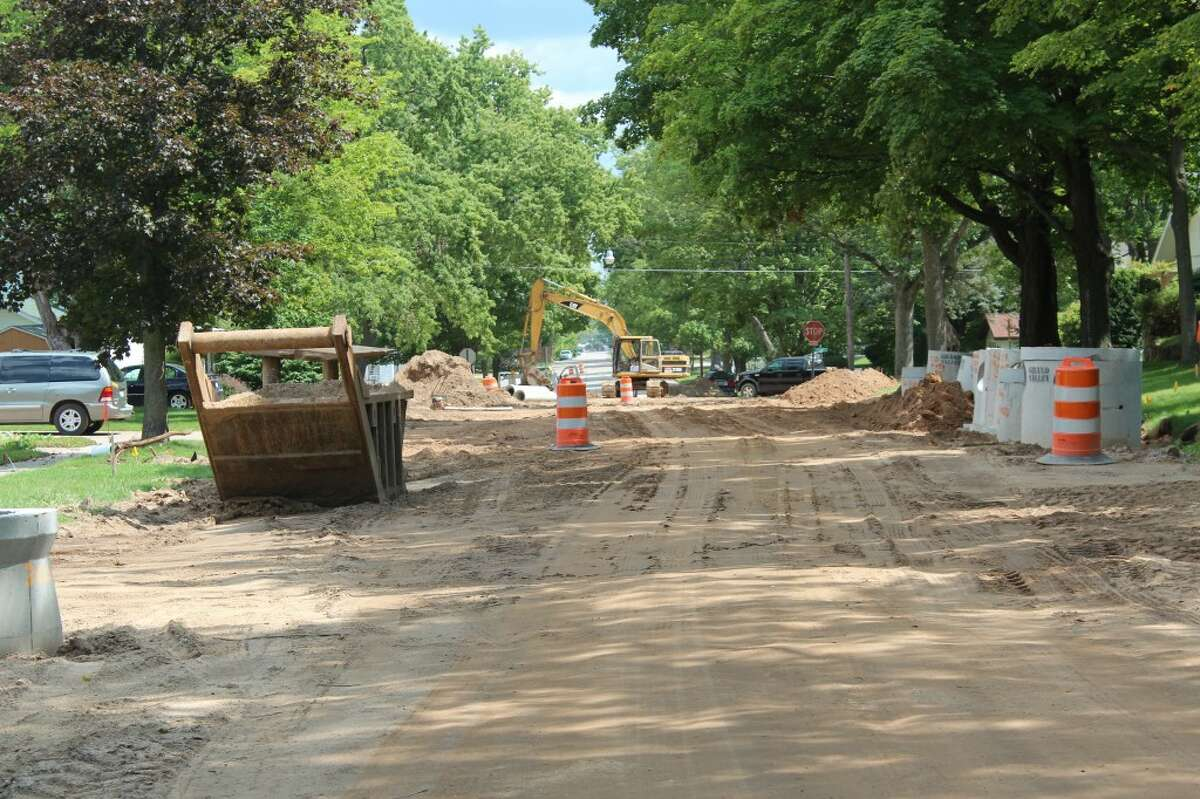 SHAPING CURBS: A curb machine shapes wet concrete to form 6-inch deep curbs on Aug. 15. After the curbs were installed, homeowners had to wait a week to use their driveway.