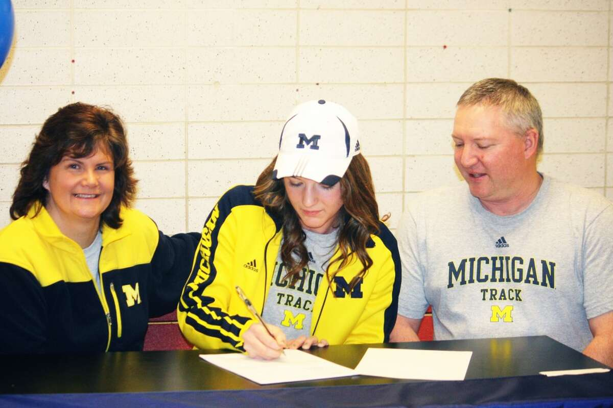 TIME TO SIGN: Vikki (left) and Brent Michell watch as their daughter, Sami Michell of Reed City signs her national letter to run track at Michigan. (Herald Review photo/John Raffel)