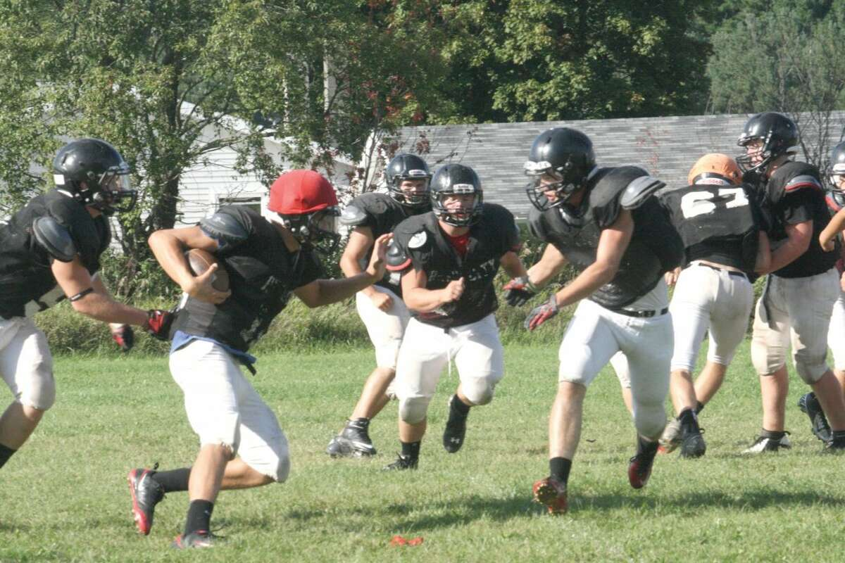 RUNNING STRONG: Reed City football players work on a running play during a Monday practice. (Herald Review photo/John Raffel)