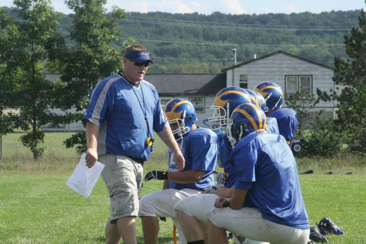 BACK TO WORK: Pat Craven, Evart football coach, talks strategy with his players at a Monday practice. (Herald Review photo/John Raffel)