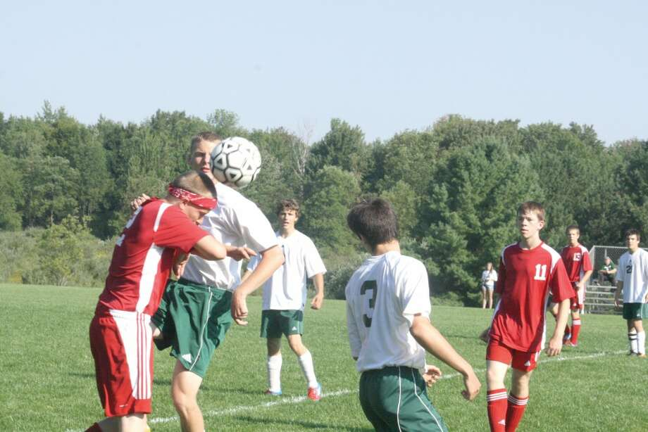 HEAD-TO-HEAD: Players go after the ball in a Pine River-Benzie Central match on Saturday. (Herald Review photo/John Raffel)