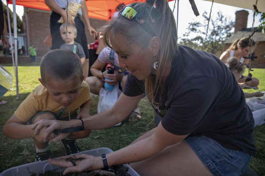 Meagan Duncan shows Walter Wise a worm at the Tinkergarten booth at the Midland Farmer's Market on Saturday, Aug. 17, 2019 at the Museum of the Southwest. Photo: Jacy Lewis/191 News