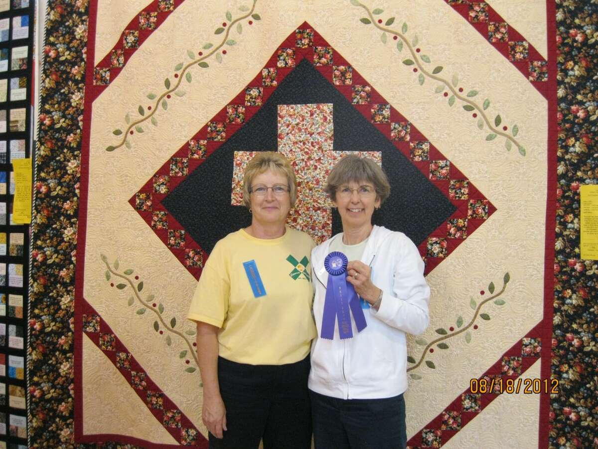 """QUILT OF HOPE: Nancy Sage (right) tied for Best of Show with her """"Quilt of Hope."""" Pictured is Sage and quilt maker Deb Sweet, who gave the quilt to Sage as a retirement gift."""