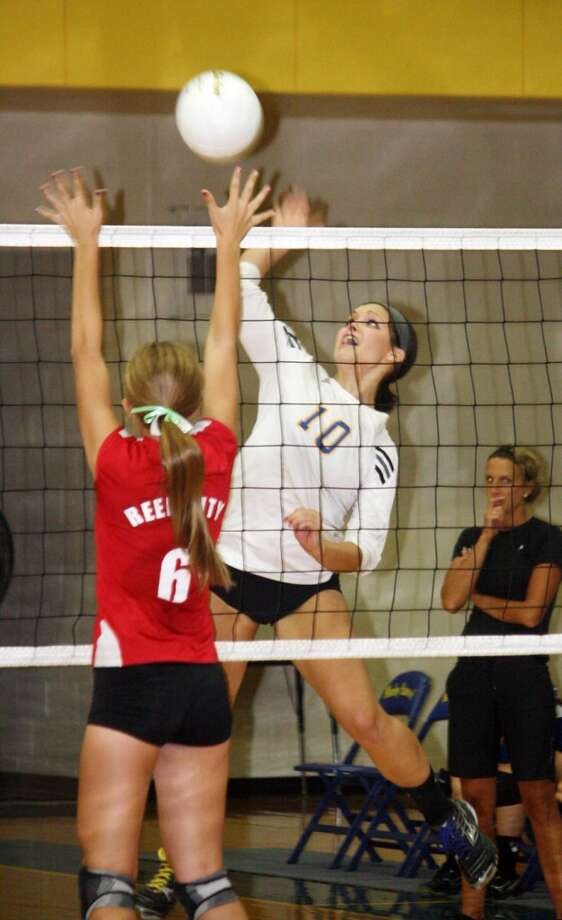ON THE ATTACK: Morley Stanwood's Brett Chesebro goes for a kill against Reed City's Heather Tacey. (Herald Review photo/John Raffel)