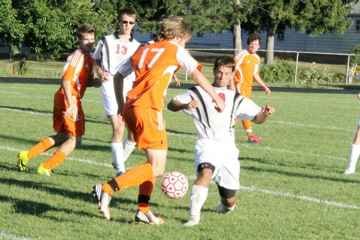 AGGRESSIVE: Reed City's Corey Saladin (right) pokes the ball away from Ludington's Carlyle Petersen (17) during Monday's soccer match at Reed City High School. (Herald Review photo/Martin Slagter)