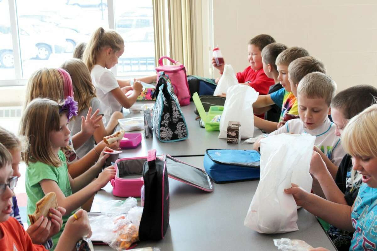 TOGETHER AGAIN: Second graders at G.T. Norman Elementary eat lunch together after school began for K-12 schools last week. Many students said they were looking forward to learning, seeing friends and recess throughout the school year. (Herald Review photo/Sarah Neubecker)