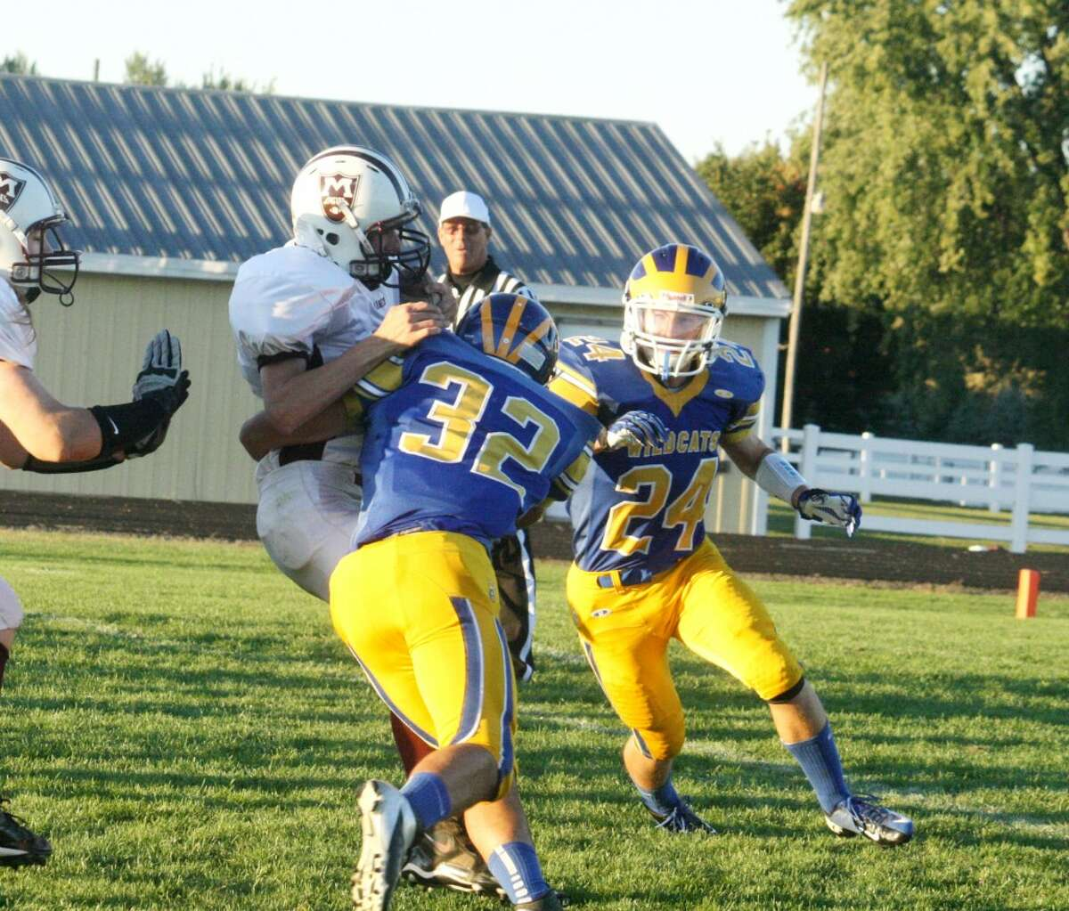 WRAPPED UP: Evart's Austin Grein (32) wraps up a Marion ball carrier during Friday's football contest at Evart High School. (Herald Review photo/John Raffel)