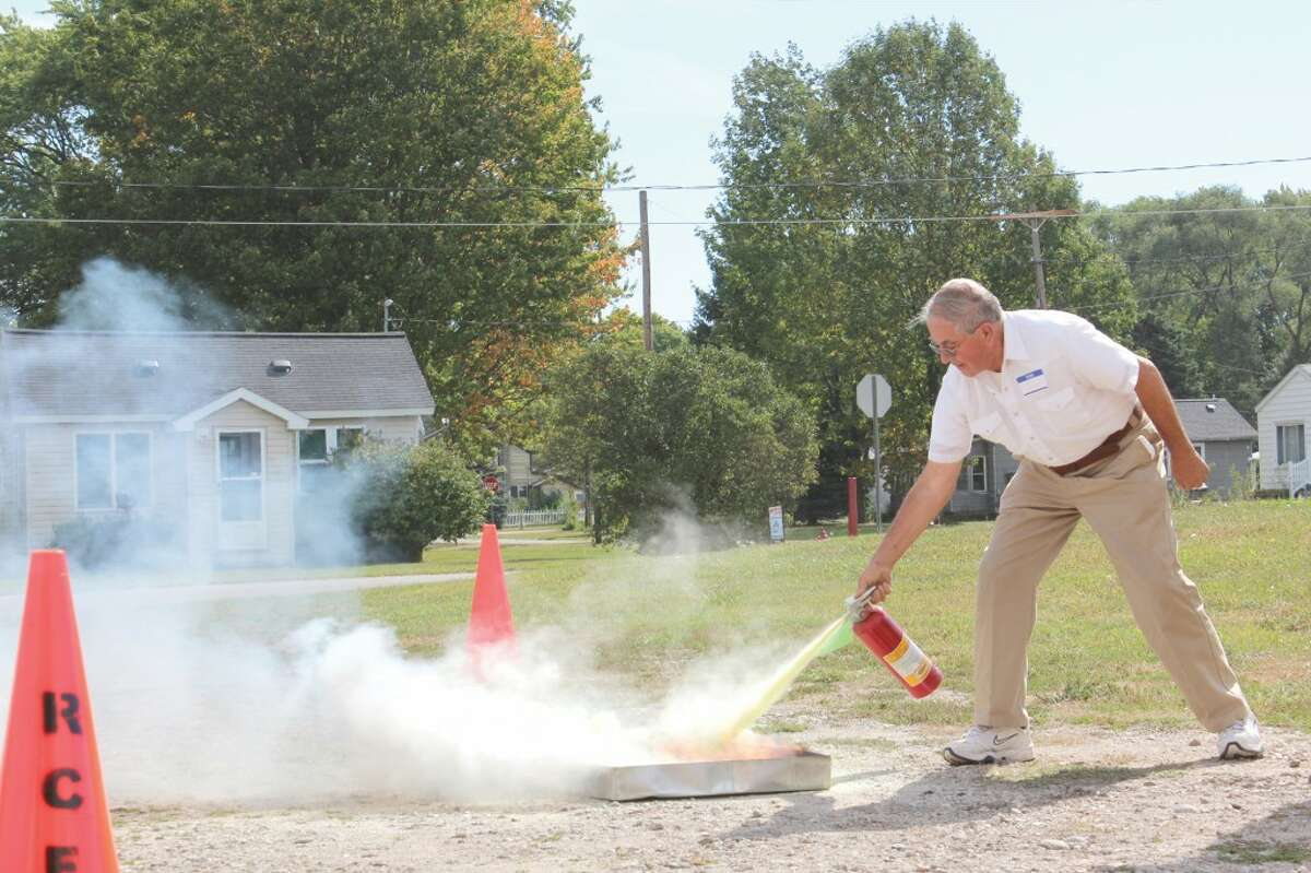 FIRE SAFETY: Frank Gondek, 77, puts out a fire during a demonstration at Camp 9-1-1. Senior citizens learned how to best prepare for and react in emergencies among other important information during the educational day. (Herald Review photo/Sarah Neubecker)