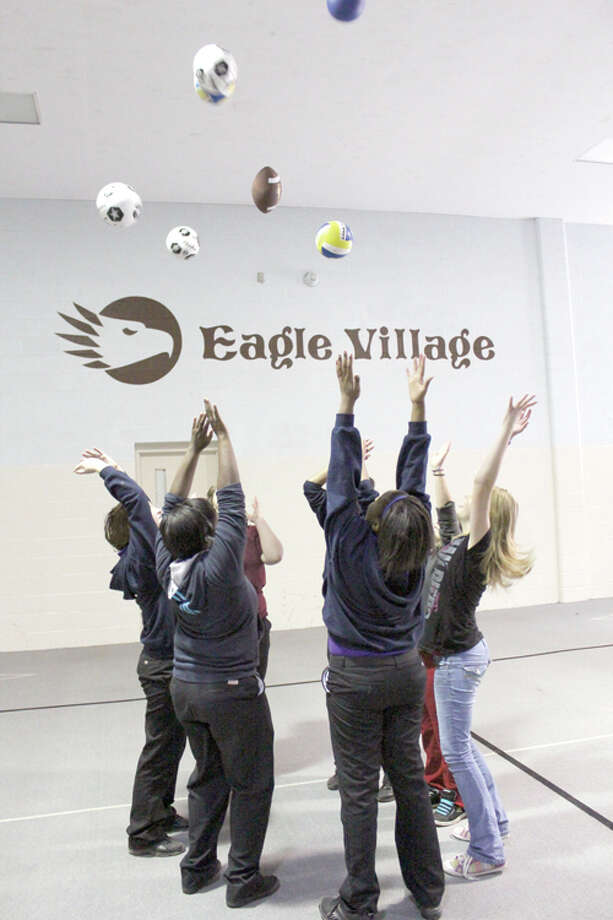 SPORTS GALORE: Students at Eagle Village toss various types of balls into the air. The equipment arrived at the school last week after Chemical Bank donated $2,000 to the school. (Herald Review photos/Sarah Neubecker)