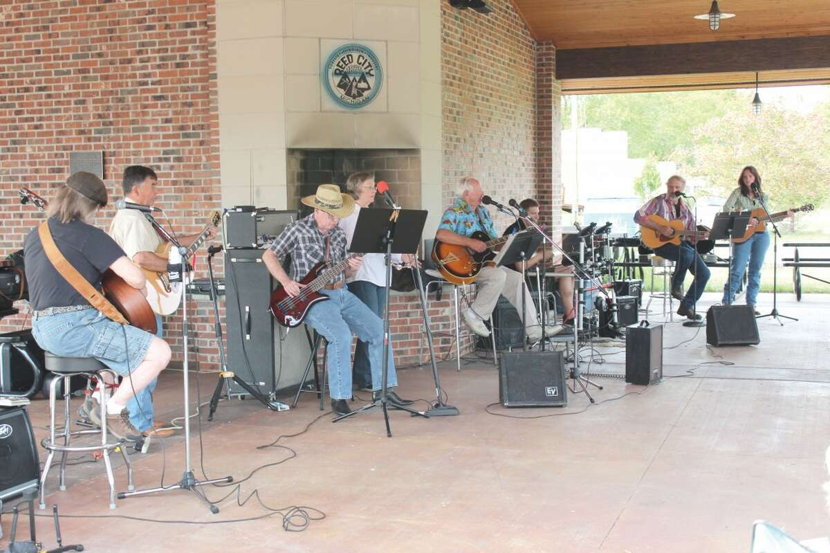 DEPOT CREW: Ron Ouderkirk, center, leads a group of local musicians in serenading crowds at the Reed City Depot. The group plays music ranging from old gospel hymns to new rock favorites. (Herald Review file photo)