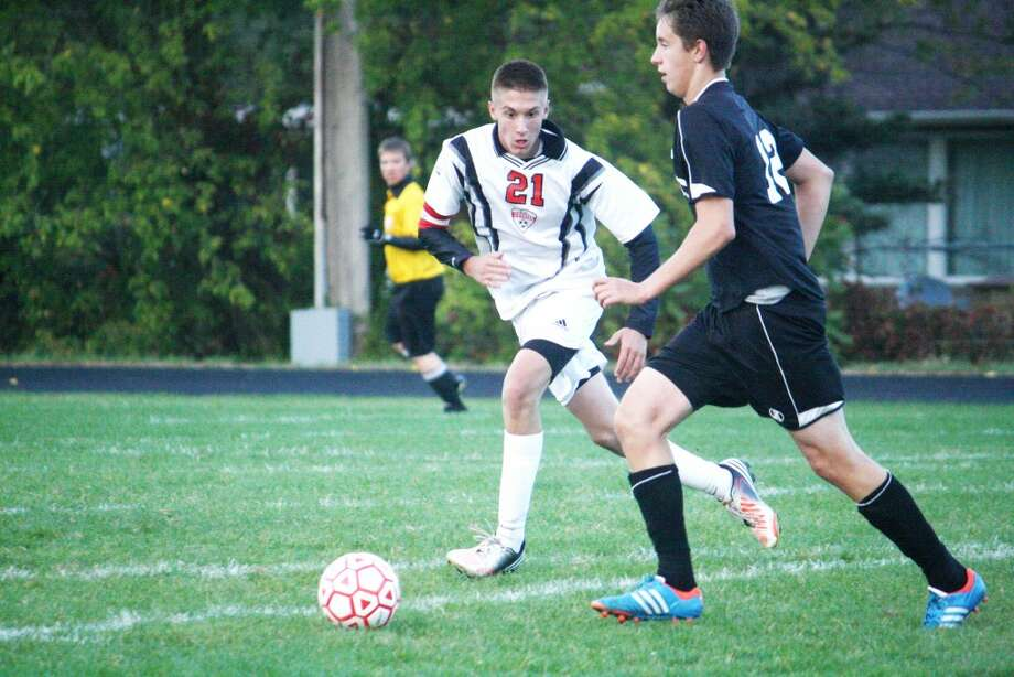 PLAYING D: Reed City's Trevor Nelson closes in on a Newaygo player during Tuesday's boys soccer match at Reed City. (Herald Review photo/John Raffel)