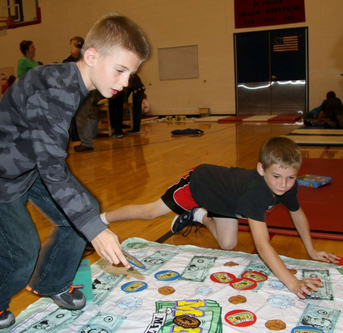 MATH GAMES: Second graders Ty Kailing (left) and Teddy Szymanski play a game where they had to cover different amounts of money shown on dice.