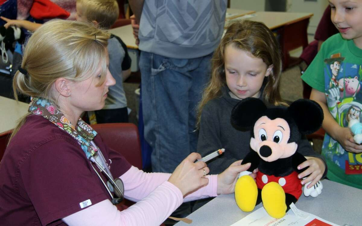 TEDDY BEAR CLINIC: A Spectrum Health Reed City Hospital nurse gives a girl's Mickey Mouse stuffed animal a shot. Spectrum hosted a teddy bear clinic to teach children what it's like to go to the doctor.