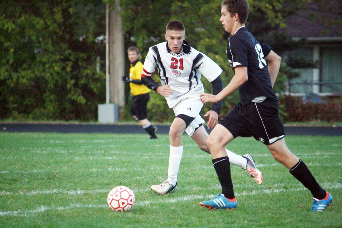 GOING FOR THE STEAL: Reed City's Trevor Nelson (21) goes after the ball against Newaygo last week. (Herald Review photo/John Raffel)