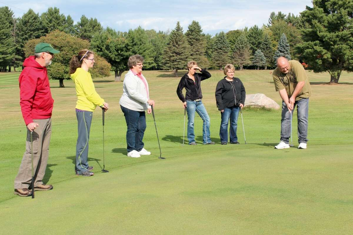 PUTTING CONTEST: Leaders watch as Evart Mayor Eric Schmidt putts at Spring Valley Golf Course. The first session of the 2012-13 Osceola Leadership Summit was held on Sept. 21 and 22.