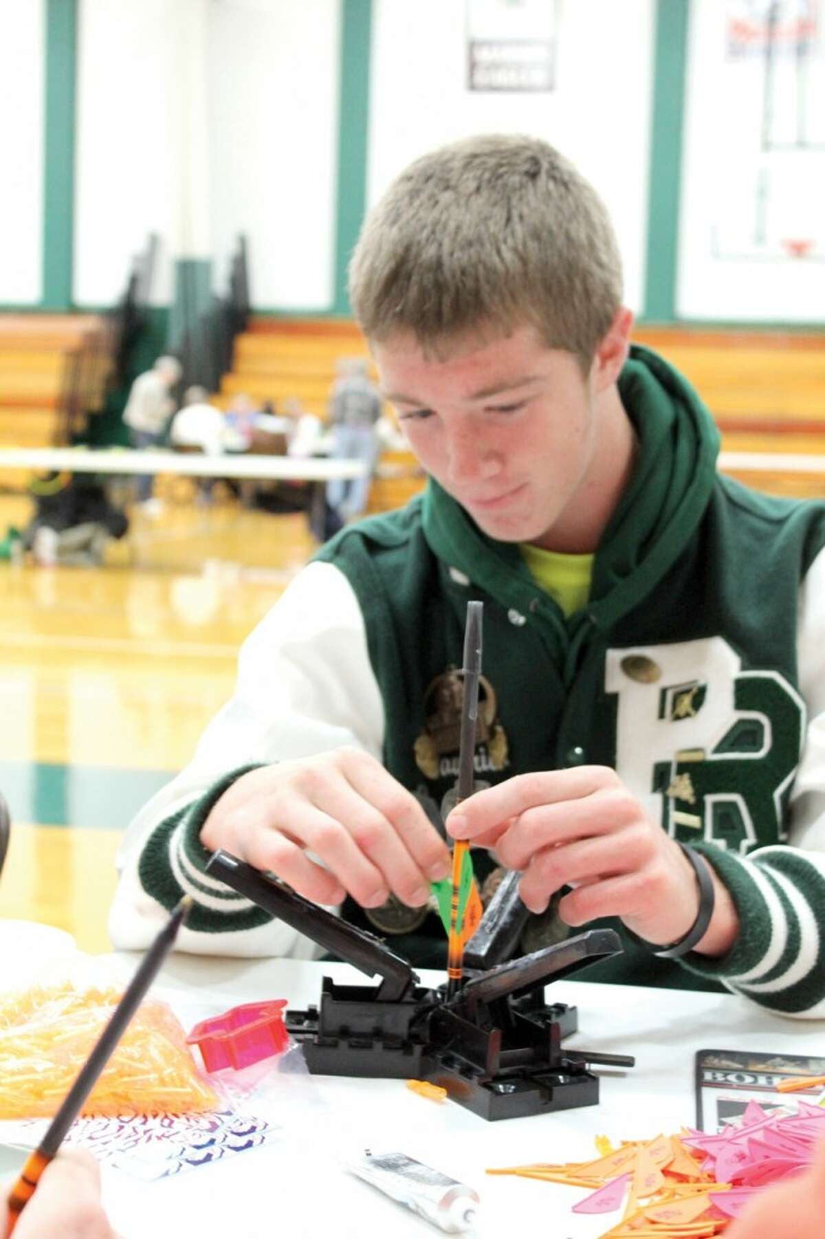 ARROW MAKING: Pine River High School senior Maverick Martin makes an arrow with a ball-point pen and feathers. Students put super glue on the arrows and pressed them together for 30 seconds. (Herald Review photo/Sarah Neubecker)