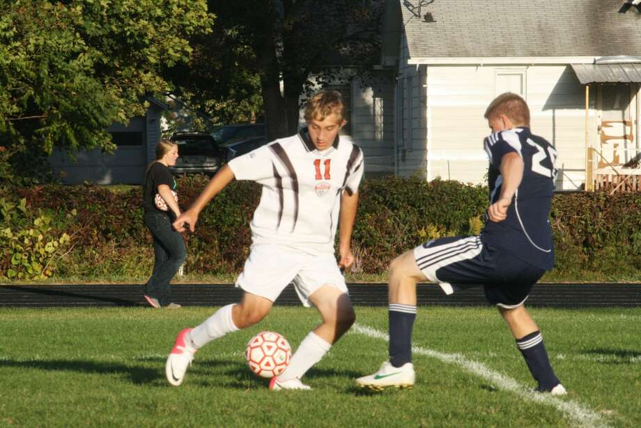 FOOTWORK: Reed City's Quinten Kichak (11) concentrates on the ball as he tries to pass a Lakeview defender during Tuesday's high school soccer action at Reed City High School. (Herald Review photo/John Raffel)
