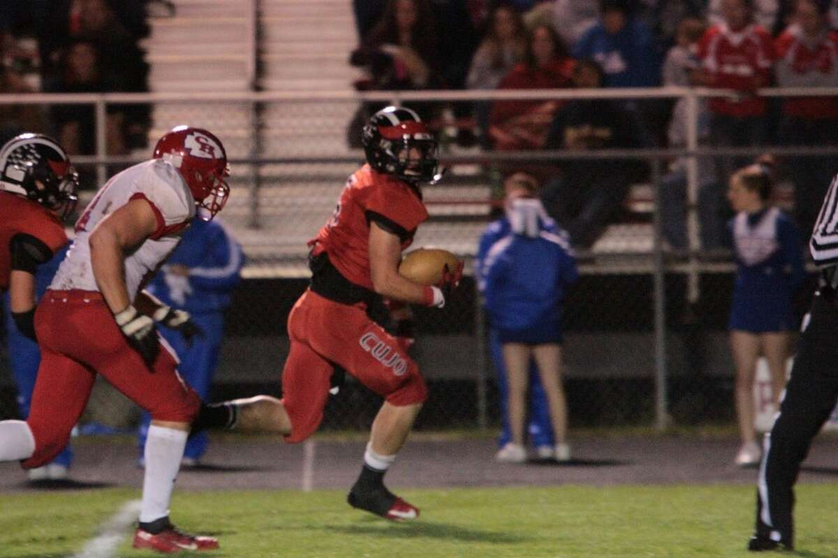 TO THE HOUSE: Reed City's Garrett Benson picks up a fumble and returns it for a touchdown during Friday's football game with Chippewa Hills. (Pioneer photo/Justin McKee)