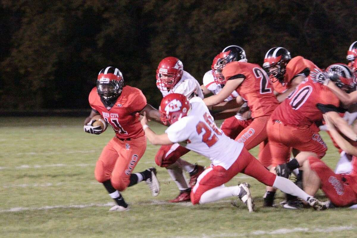 PRESSING FORWARD: Reed City's Paris Jones (11) tries to escape from the Chippewa Hills defense. (Herald Review photos/Justin McKee)