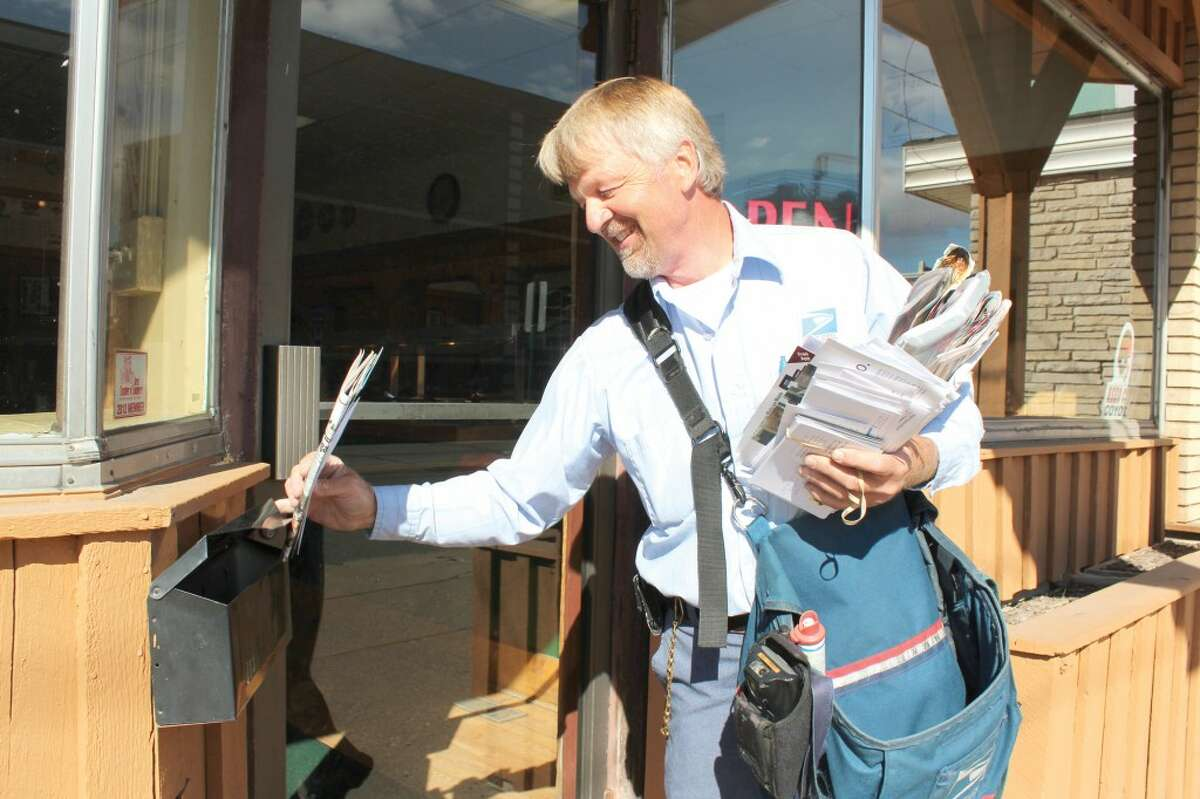 MAIL TIME: Long-time mail carrier Bill Rogers makes a delivery to Pompeiis Pizza in downtown Reed City. Rogers said if he wasn't he the mail business, he would like to be a farmer. (Herald Review photo/Sarah Neubecker)
