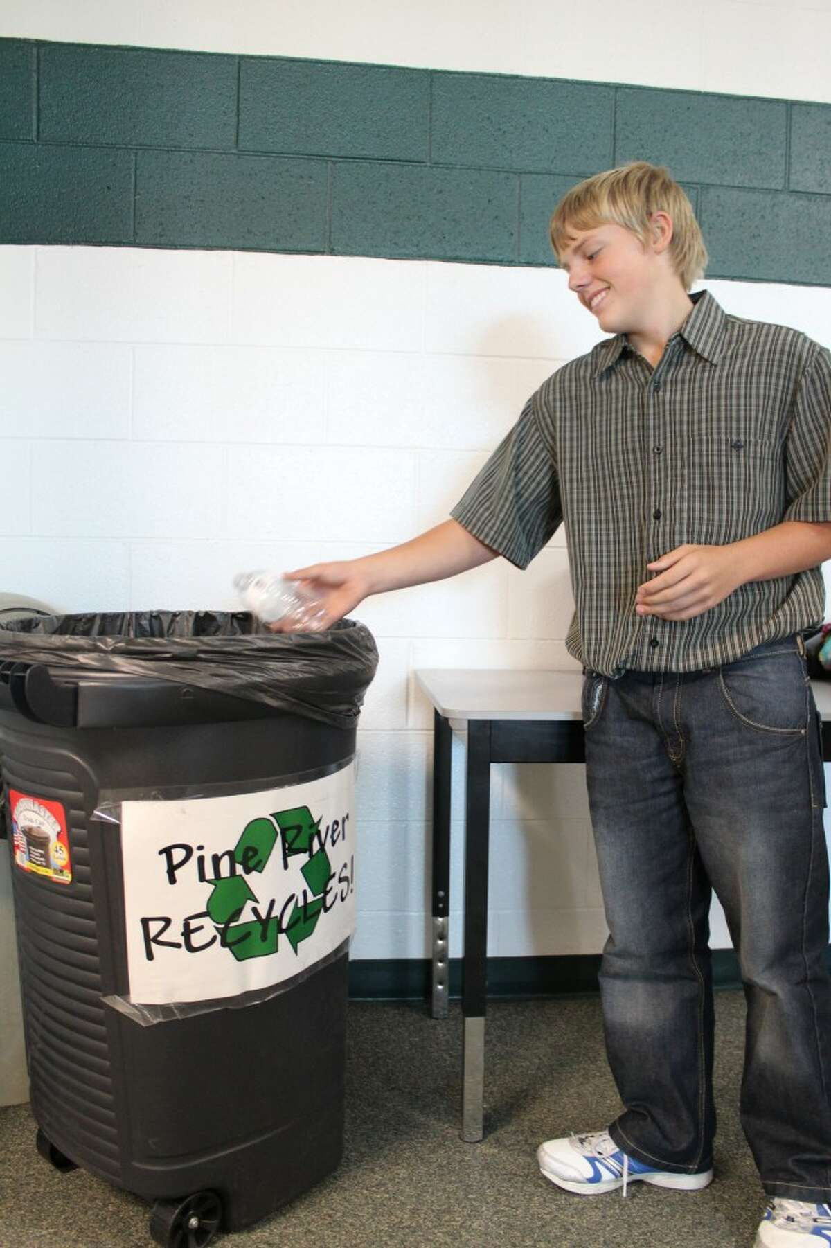 PINE RIVER RECYCLES: Brian Hutchinson, eighth grader at Pine River Middle School recycles a water bottle in one of the school's recycling bins. Pine River High School joined the middle school in the green initiative this year. (Herald Review photo/Sarah Neubecker)