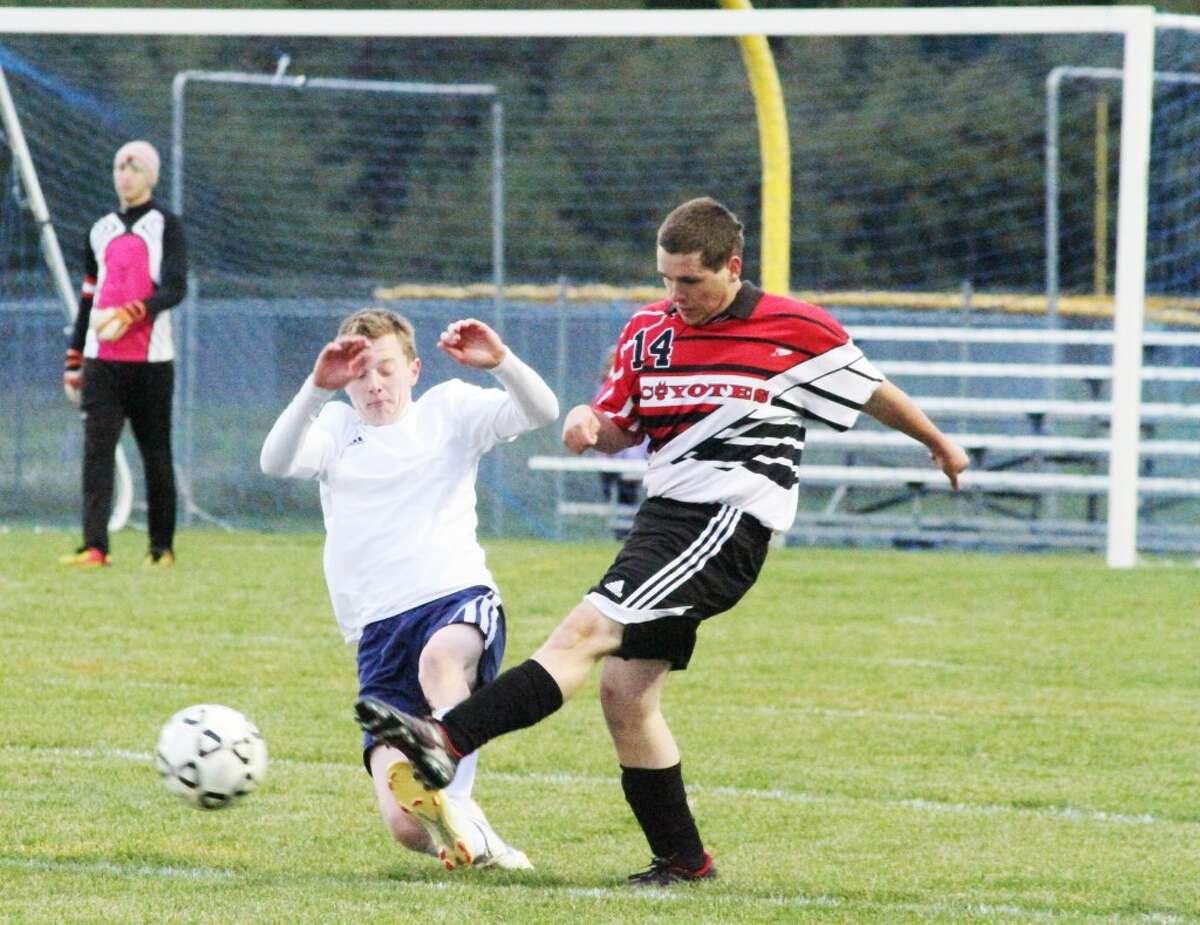 BOOTED: Reed City's Seth Poirot (14) kicks the ball away from a Manistee player during Monday's boys soccer contest. (Pioner News Network photo/Dylan Savela)