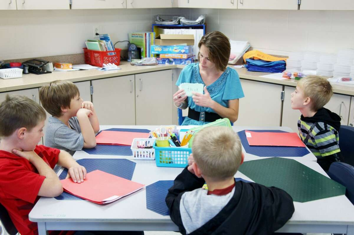 SMALL GROUP: General classroom teacher Tracy Hansen works with a group of her second-grade students to go over vocabulary word flashcards. General classroom teachers work closely with RTI teachers to offer students the individualized attention they need.