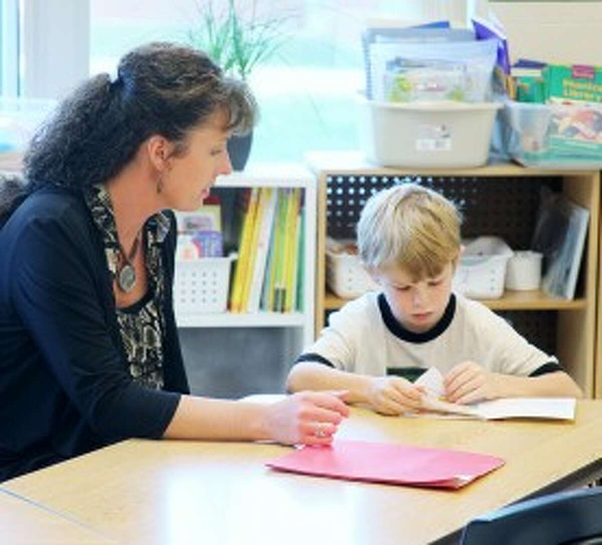 RESPONSE TO INTERVENTION: (On left) Vicky Bowman, a Response To Intervention teacher at G.T. Norman Elementary School, helps a second grader review some reading skills. The Response To Intervention program identifies specific skills students struggle with and provide support to help those students improve. (Herald Review photos/Lauren Fitch)