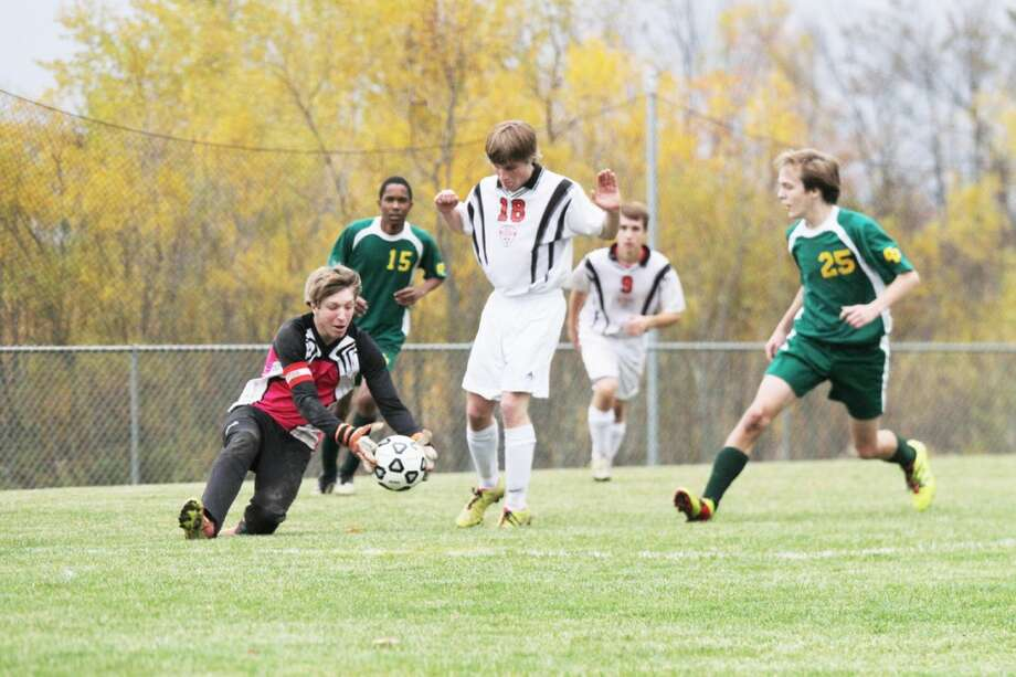FIRST TO THE BALL: Reed City keeper Ben Schermerhorn (left) gets to the ball ahead of teammate Quinton Kichak (18) and a Comstock Park player during Wednesday's boys soccer match at Pine River High School. (Herald Review photo/Bob Allan)
