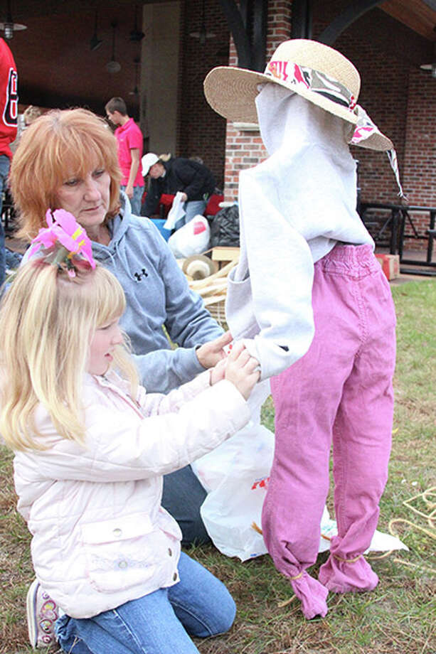 SCARECROW DECORATING: Dani Trochelman (right) helps her granddaughter Lillian, 5, stuff a scarecrow with plastic bags during a scarecrow decorating contest at the Reed City Fall Festival. The event also featured hay rides, kids games and an appearance by Dynamite the Clown. (Herald Review photo/Jonathan Eppley)