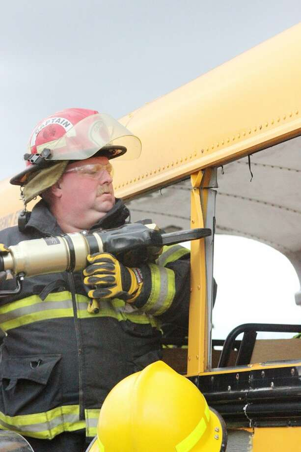 JAWS OF LIFE: Capt. Rick Ball, of the Lincoln Township Fire Department, uses the Jaws of Life to cut into a school bus during a bus extrication exercise on Saturday in Reed City. (Herald Review photos/Jonathan Eppley)