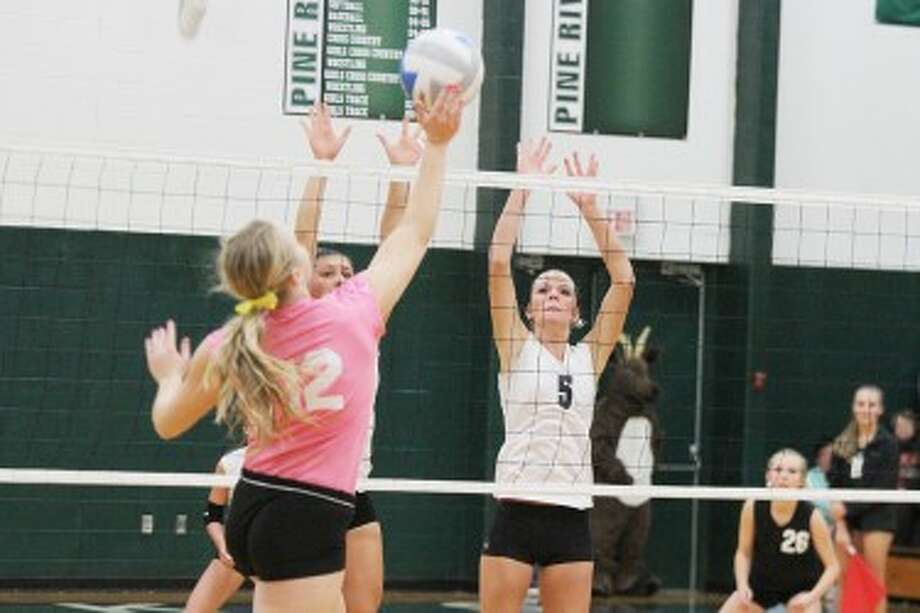 SOLID D: Miriah Holmes (left) and Jamie Justin (5) go up for the block in Pine River's home game with McBain last week. (Herald Review photo/Martin Slagter)