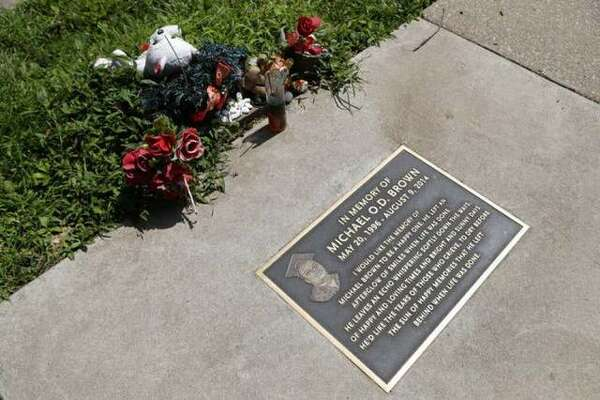 Flowers and other items lie near a memorial plaque in the sidewalk near the spot where Michael Brown was shot and killed by a police officer five years ago in Ferguson, Missouri.