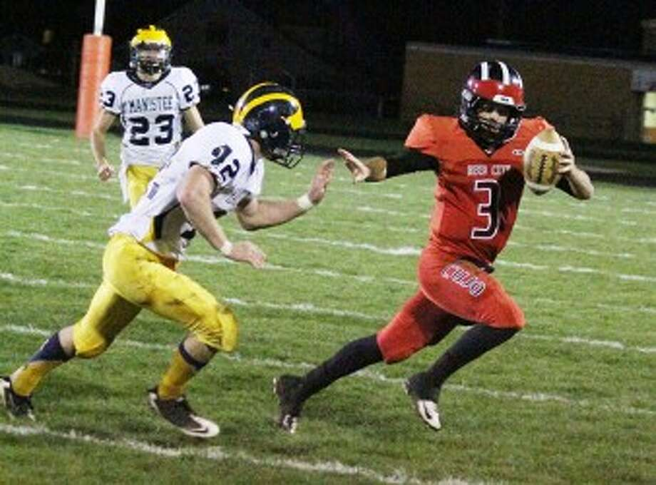 GET OUT OF MY WAY: Reed City quarterback Chad Samuels (3) picks up some yards before being tackled by Manistee's Lane Gancaraz during Friday football action. (Pioneer News Network photo/Matt Wenzel)