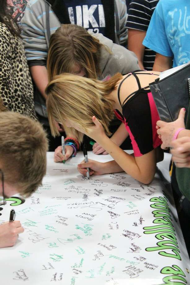 TAKING THE CHALLENGE: Pine River High School Students sign a banner saying they will take the Kids Driving Responsibly challenge in honor of Kelsey Dawn Raffele, who was killed in a car accident while talking on her cell phone.