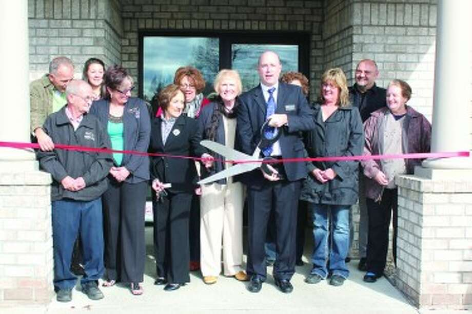 RIBBON CUTTING: Members First CEO Eric Brubaker cuts a ribbon to recognize the merger between Central Michigan Community Federal Credit Union and Members First Credit Union at the Evart credit union, located at 201 E. 7th St. in Evart. The business has been operating under the Members First leadership since June. (Herald Review photo/Sarah Neubecker)