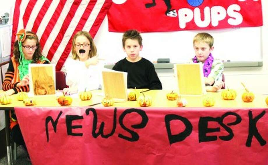 NEWS ANCHORS: Fifth graders Taylor Harrison, Alaina Stein, Jared Karns and Kyle Roggow serve as news anchors for the Coyote Pup News, filmed in Robbie Svegel's class at G.T. Norman Elementary. (Herald Review photos/Sarah Neubecker)