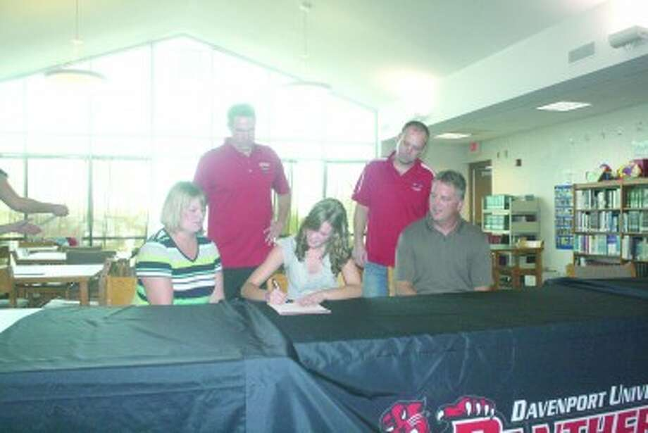 LETTER OF INTENT: Jamie Justin, with her parents, Paula and Ken Justin at her side, signs a letter of intent last week to play basketball at Davenport University. In back are, left, Davenport coach Mike Williams and Pine River coach Shawn Ruppert. (Herald-News photo/John Raffel)