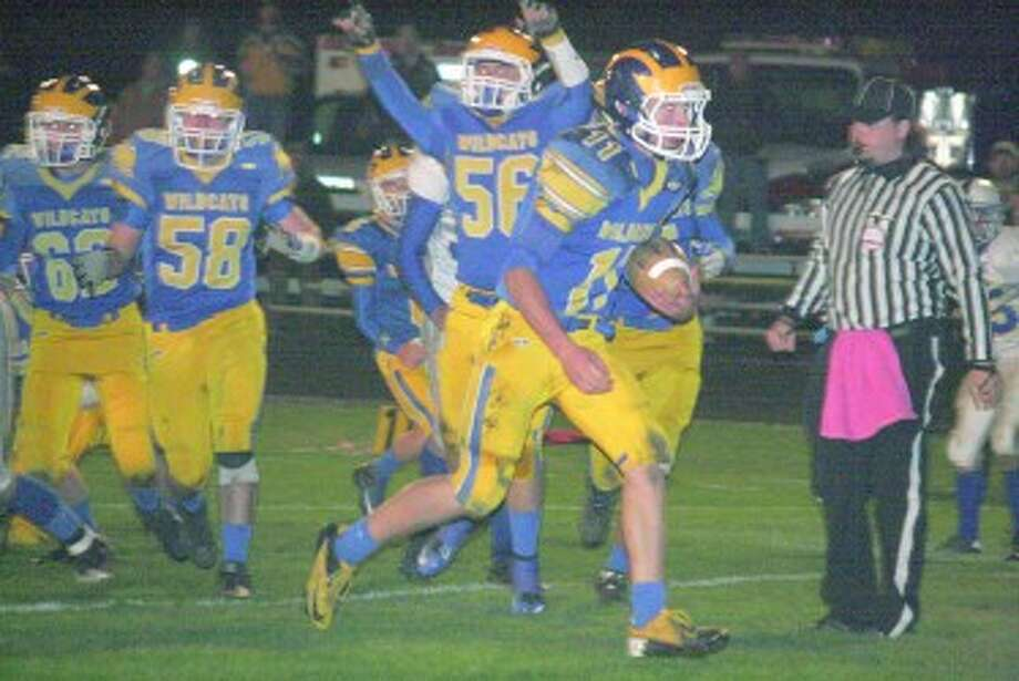 IN FOR THE SCORE: John Danley runs to the end zone for Evart as teammates Jake McKinstry (56) and Dean Marsh (58) celebrate. (Herald-Review photo/John Raffel)