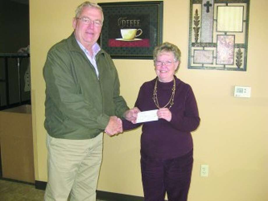 SUPPORTING GOD'S KITCHEN: Tom Eichenberg, Grand Knight of the Knights of Columbus of Council No. 12668 in Reed City, presents a check to Bernice Graham of God's Kitchen at the Reed City Church of the Nazarene. (Courtesy photos)